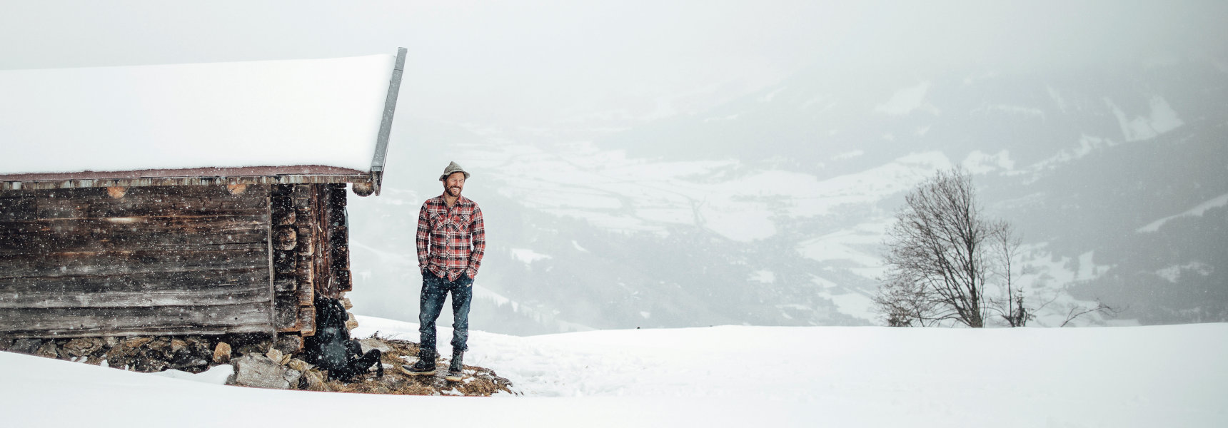 Outdoor cook Markus Sämmer stands in front of a snowy hut in the mountains