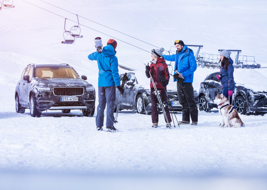 Group of skiers stands in front of cars
