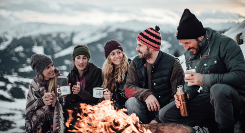 Markus Sämmer sits with friends around a campfire and warms himself with a dish from a thermos flask.